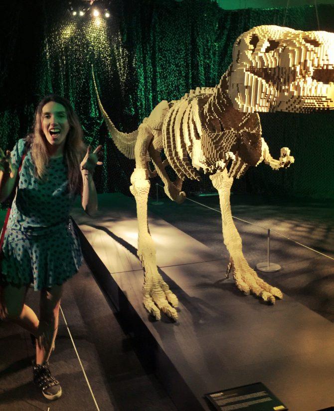 Fefê Rosada com um dinossouro de feito com lego na exposição The Art of the Bricks, exposição Lego.