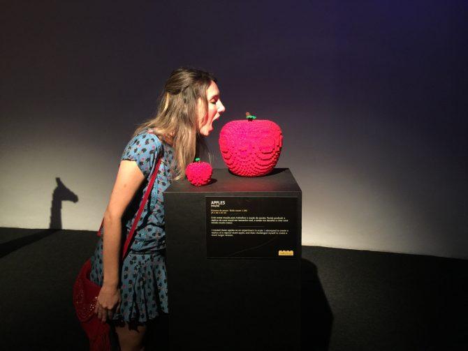 Fefê Rosada comendo a maçã na exposição The Art of the Bricks, exposição Lego.